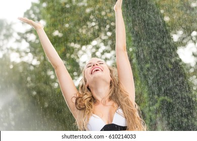 Happy woman standing in the summer rain with raised hands