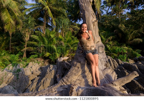happy woman standing under a tree against the palm trees, happily spends a holiday in an exotic country