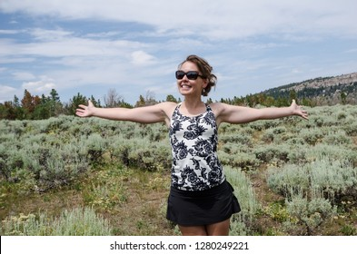 Happy woman stands in a field of high desert sagebrush and creosote bushes in rural Wyoming