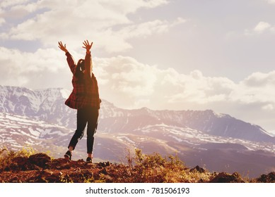 Happy woman stands with raised hands on background of sunset in mountain's range