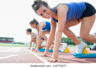 Happy woman at starting blocks on track field