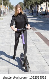 Happy woman starting an electric scooter
