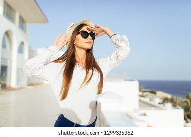 Happy woman with straw sunhat looking to the sea view from balcony