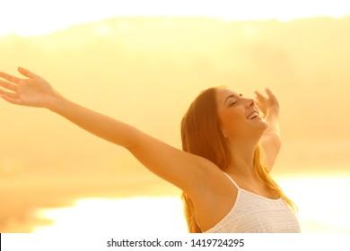 Femme heureuse tenant les bras respirant un air frais au coucher du soleil sur la plage