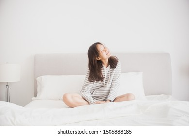 Happy Woman stretching in bed after wake up. White bedroom tone. Smiling to the sunrise in the morning.