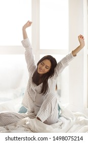 Happy woman stretching in bed. Attractive Asian girl in nightgown sitting against big window and waking up in the bedroom on sunny morning. Good morning concept.