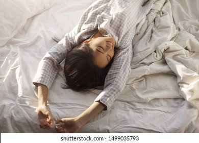 Happy woman stretching in bed in the morning. Attractive Asian girl in nightgown waking up in the bedroom on sunny morning. Good morning concept
