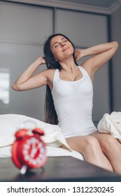 Happy woman stretching in bed. Red alarm clock on foreground