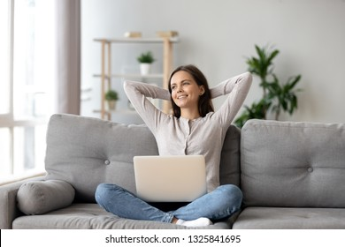 Happy woman stretching hands, relaxing on cozy sofa with laptop in living room at home, smiling girl resting after finished computer work, dreaming, thinking about good future, break