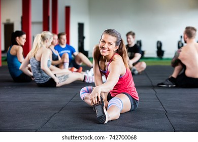 Happy Woman Stretching While Friends Sitting In Background