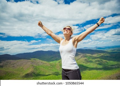 Happy woman successfully hiking Old Rag mountain in Shenandoah National Park in Virginia
