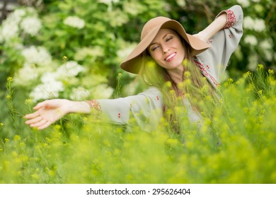 Happy woman in summer field. Young girl relax outdoors. Freedom concept