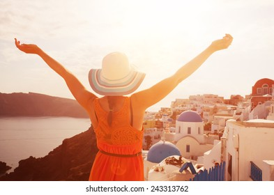 Happy woman in sun hat enjoying her holidays on Santorini, Greece. View on Caldera and Aegean sea from Oia. Active, travel, tourist concepts