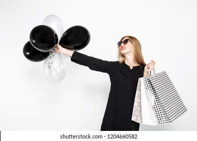 happy woman in sunglasses in black dress and with red lips holding bags and black balls, satisfied girls after shopping, Black Friday on white background