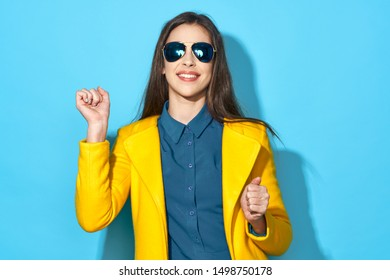 Happy woman in sunglasses and a blue shirt yellow jacket cropped view