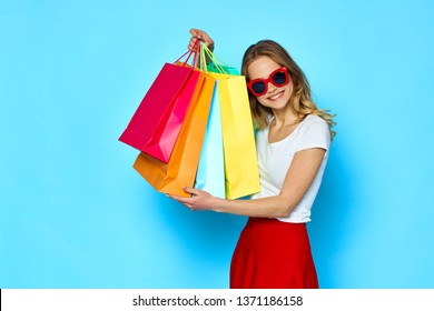 A happy woman in sunglasses is holding multicolored packages in her hand on a blue background