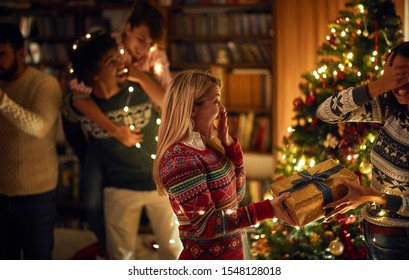 Happy woman surprising her friend girl with a romantic present at Christmas.