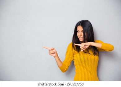 Happy woman in sweater showing finger away over gray background