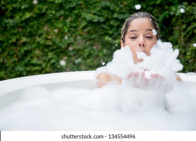 Happy woman taking a bubble bath and being playing with foam