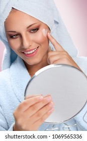 Happy woman taking care of her skin with moisturizing cream