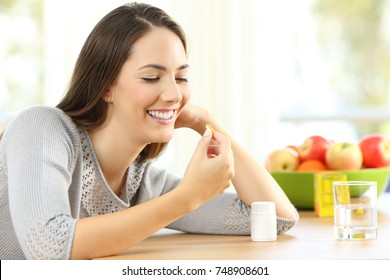 Happy woman taking omega 3 vitamin pills on a table at home with a colorful background