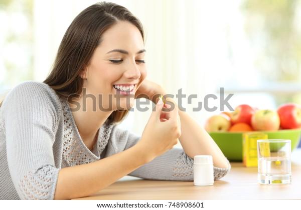 Mujer feliz tomando píldoras de vitamina omega 3 en una mesa en casa con un fondo colorido