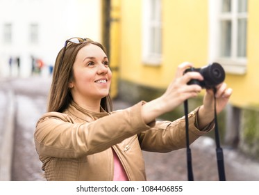 Happy woman taking photo with camera. Tourist on vacation in city street. Holiday pictures. Smiling photographer or hobbyist.