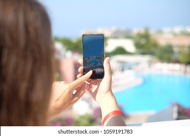 Happy woman taking photos of fantastic view with full view smartphone camera on summer travel vacation. Brunette girl with long hair standing backwards and making photography towards the swimming pool