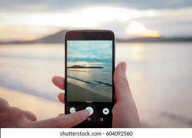 Happy woman taking photos of the sea at sunset with smartphone camera on summer travel vacation to the coast, Phuket island, Thailand. Girl making photography towards ocean. Sea view on phone photo