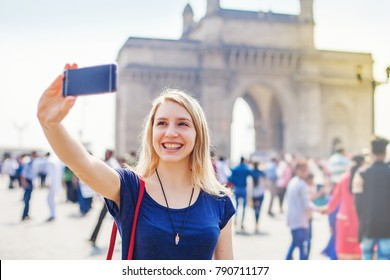 Happy woman taking selfie in front of Gateway of India