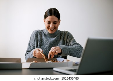 Happy woman taking a slice of pizza while sitting in front of laptop.