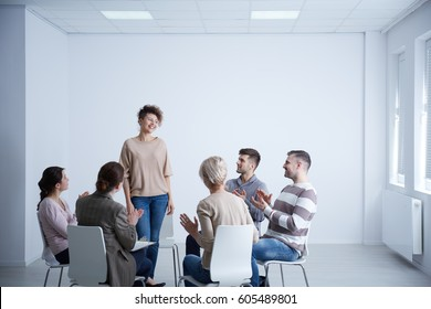 Happy woman talking in front of group during psychotherapy
