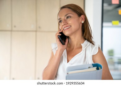 Happy woman talking on cell phone, smiling and holding a personal notebook.