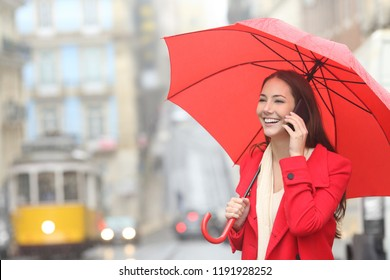 Happy woman talking on phone holding a red umbrella under the rain in winter