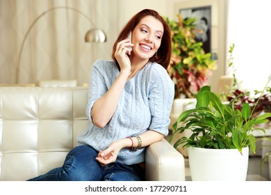 Happy woman talking on the phone and looking away at home
