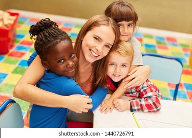 Happy woman as a teacher or childminder together with children in the day care center