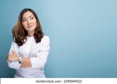 Happy woman thinking and standing isolated over blue background