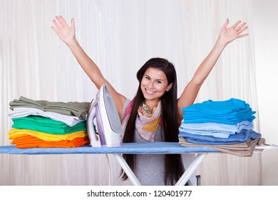 Happy woman throws her arms in the air because she has finished and folded all of the ironing