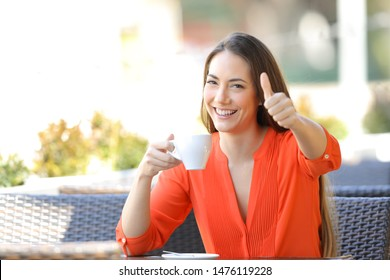 Happy woman with thumb up in a bar holding a coffee cup sitting in a restaurant terrace