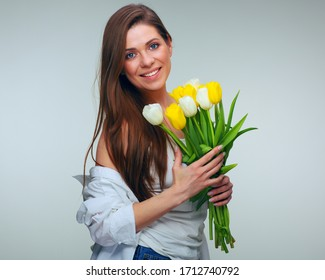 Happy woman with toothy smile dressed casual white shirt holding flowers. isolated female portrait.