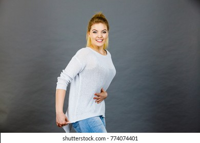 Happy woman touching her stomach and back feeling fit and slim after weight loss.