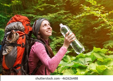 Happy woman tourist with backpack. Young tourist girl drinking water in forest with sunshine. Female with bottle
