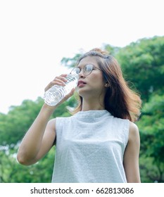Happy woman tourist drinking water in nature