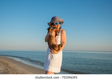 Happy woman tourist, in a funny sunglasses, with a small dog in her arms is posing on deserted beach during sunset and having fun. Wonderful vacation on a seaside.