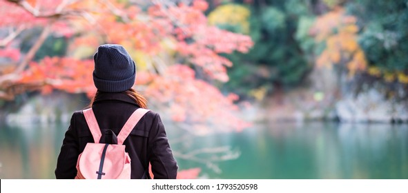 Happy woman tourist looking colorful leaves and Katsura river in Arashiyama, young Asian traveler visit in Kyoto and enjoy travel in Japan. Fall Autumn season, Vacation,holiday and Sightseeing concept
