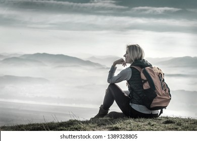Happy woman tourist sitting on the green grass on the peak of mountain and look on the nice fog view. Concept freedom.