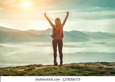 Happy woman tourist stay with open hands up on the green grass on the peak of mountain and look on the nice fog view. Concept freedom.