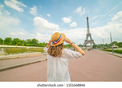 Happy woman tourist travel in Paris with eiffel tower and beautiful blue sky, she feel happy and free. caucasian beauty wearing hat with french flag
