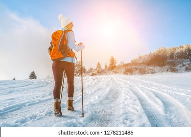 Happy woman tourist walking on the snowy trek on the peak of mountain and look on the nice winter view in sunny cold day. Concept travell and freedom.