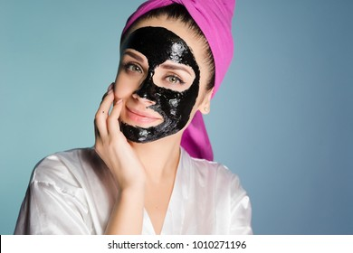 happy woman with a towel on her head apply a cleansing mask on the face skin